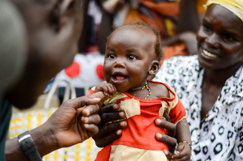 "Six-month-old Cecilia sits in her mother Helen's lap as they wait to receive $45, a monthly payment for Helen's participation in a six-month business training program by World Vision in Juba, South Sudan. Helen likes the Cash for Training project, which was set up to help vulnerable families cover their needs and to combat hunger, ""because its gives us money to make our own choices,."" she says. (©2017 World Vision/photo by Mark Nonkes)"