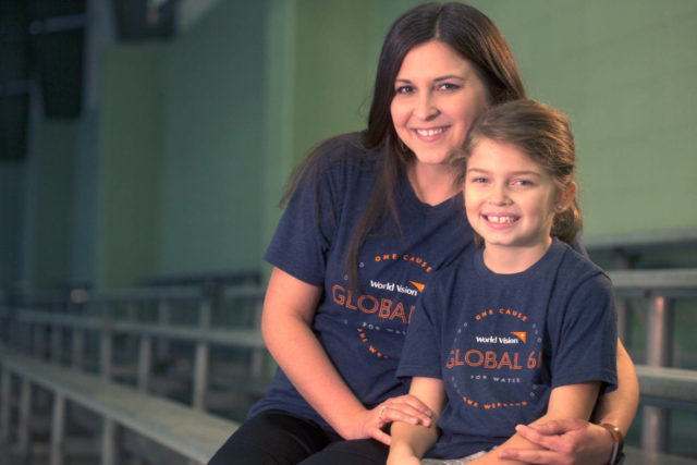 Mom and 7-year-old daughter sitting together wearing World Vision Global 6K for Water shirts.