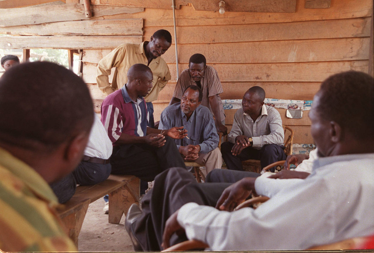 A World Vision HIV/AIDS community counselor, Menes Maruwa, explains how HIV is transmitted to a group of men at a mining camp in Tanzania. Many miners contracted the virus while working away from home at camps like this, then unwittingly infected their wives when they returned to their home communities. (©2001 World Vision/photo by Nigel Marsh)