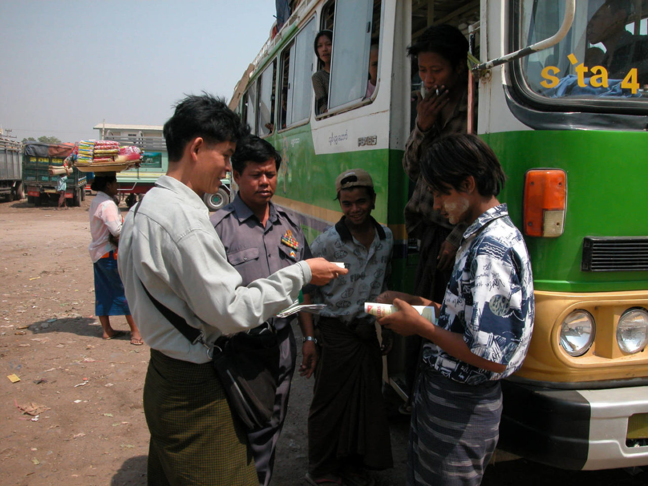World Vision Myanmar's Community Development Facilitator Saing Zaw Hmun hands out literature about the risks of HIV/AIDS to bus and truck drivers, ticket sellers, route operators and market traders at a Mandalay bus station. Because of their risky behavior, the virus spreads throughout the country along the road network. (©2004 World Vision/photo by James East)
