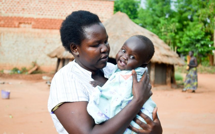 African woman holding baby, who has pneumonia.