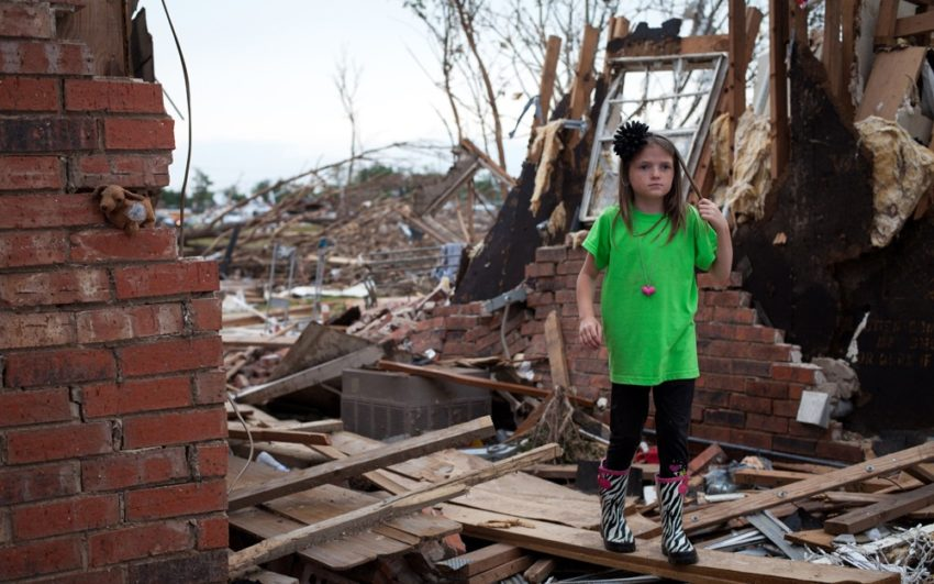 Young girl walking among destroyed home after tornado in Oklahoma.