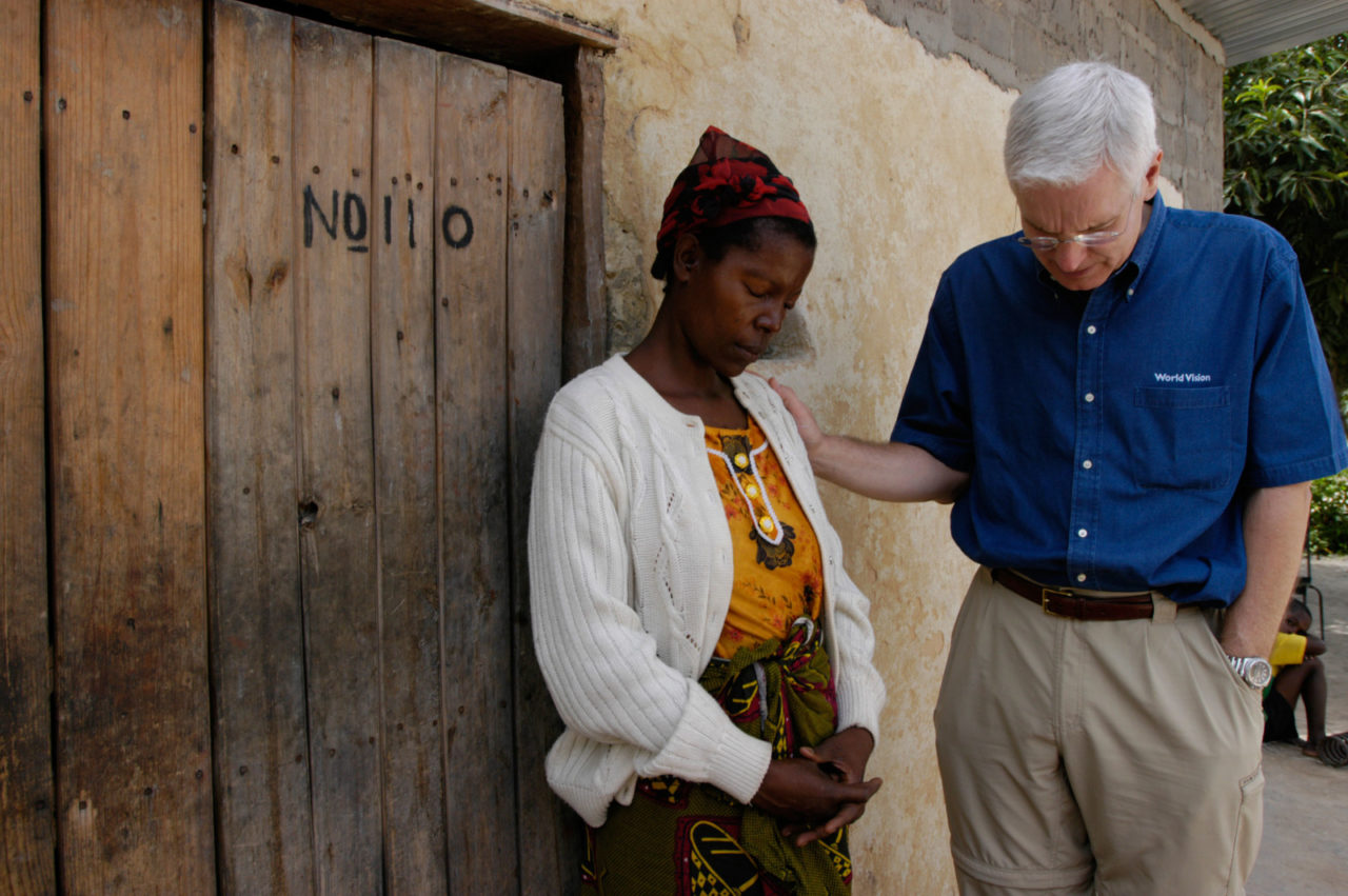 World Vision U.S. President Rich Stearns prays with HIV-positive widow Agnes Lowiji and her five children. World Vision is working to reduce the stigma of HIV in her community and helping her to care for her children. (©2004 World Vision/ photo by Jon Warren)