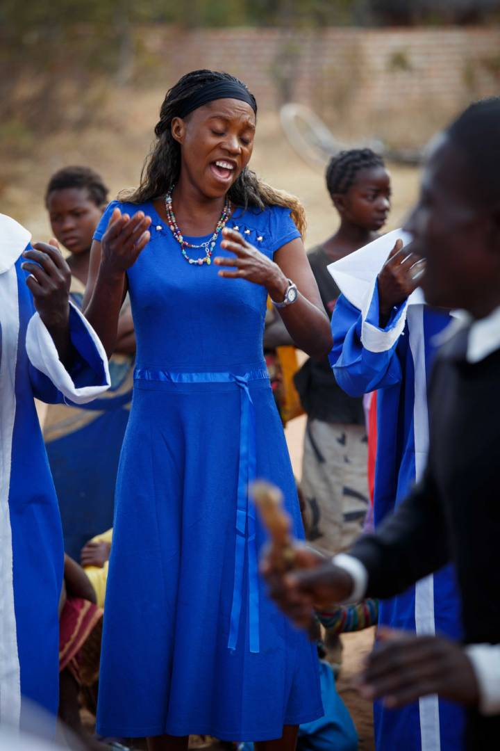 "Gift Chola sings as part of a choir in northern Zambia. Gift used to walk a third of a mile carrying her family's laundry to wash it at the closest stream. As she walked, she'd sing a song: ""I'll wait patiently for your blessings, God, I'll wait."" She says people didn't have time to attend church because of walking for water. World Vision brought clean water to her community a couple years ago. She now has time to sing in her church choir, and church attendance has more than tripled, as people now have time to attend services. (©2017 World Vision/photo by Chris Huber)"