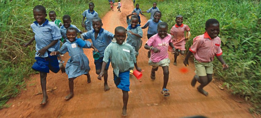 Children running in a group down a dirt road.