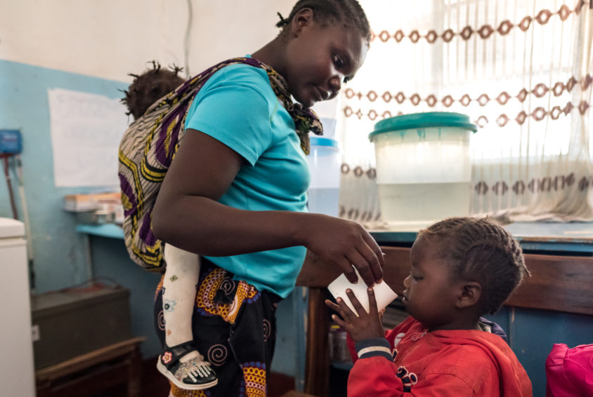 Mirriam Ngulube, 21, gives her sick daughter Nasilele, 5, water mixed with antimalarial medication at the Kahare Health Center in Nkeyema district, Zambia. World Vision provides high-demand drugs to the health center, which sometimes treats 50 patients a day for malaria. (©2018 World Vision/ photo by Eugene Lee)