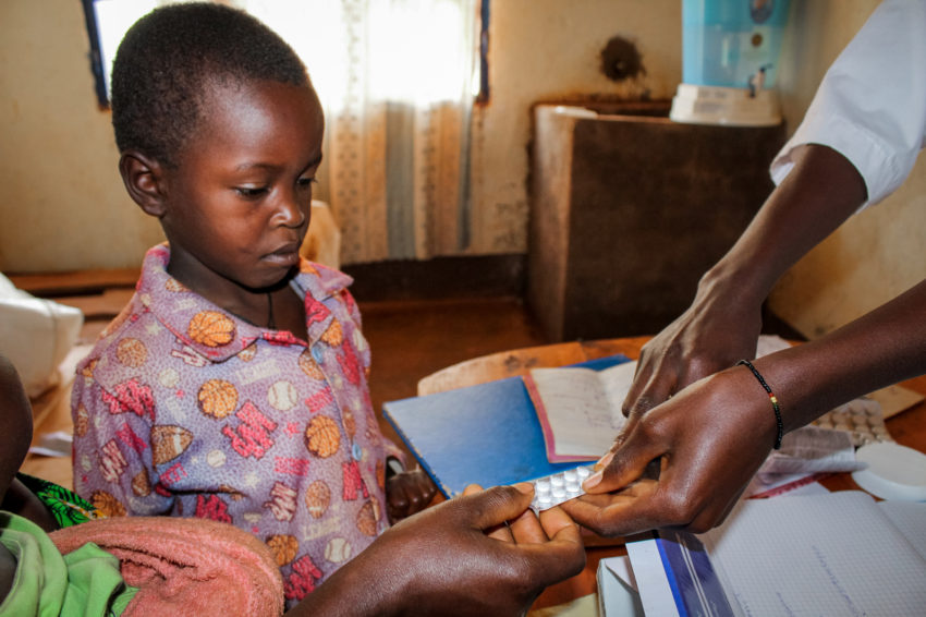 After Justin, 7, tested positive for malaria, a nurse gives his mother, Francine, his medication. World Vision has started providing bed nets and spraying for insects in three provinces of Burundi to prevent malaria's spread. (©2017 World Vision/photo by Javan Niyakire)