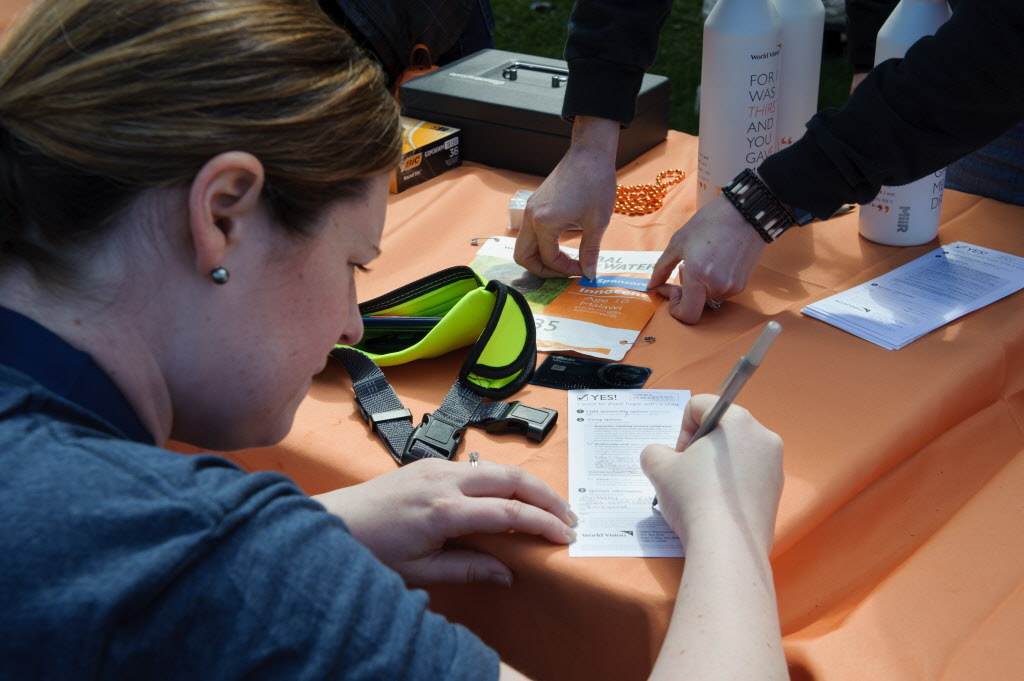 A woman kneels at the table after finishing a walk to bring clean water to people around the world. She is filling out a form to sponsor the child through World Vision.