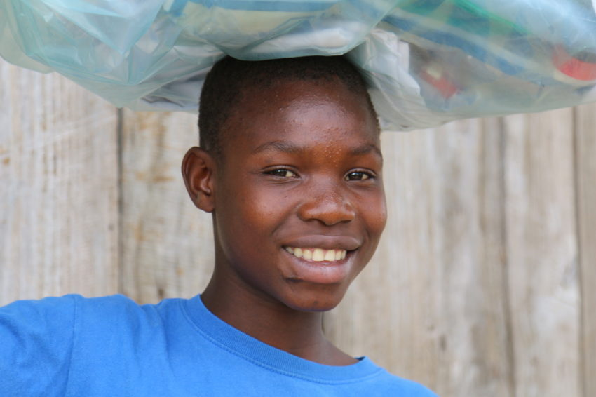Pierre, 16, carries a kit his family received after Hurricane Matthew hit Haiti in 2016. The kit contains tarpaulins, blankets, mosquito nets, a flashlight, and other household necessities. (©2016 World Vision)