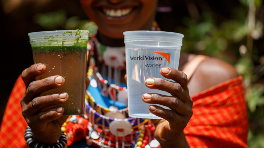 The global water crisis no more for this woman in Kenya who holds up a cup of dirty, contaminated water next to a cup of clean, safe water.