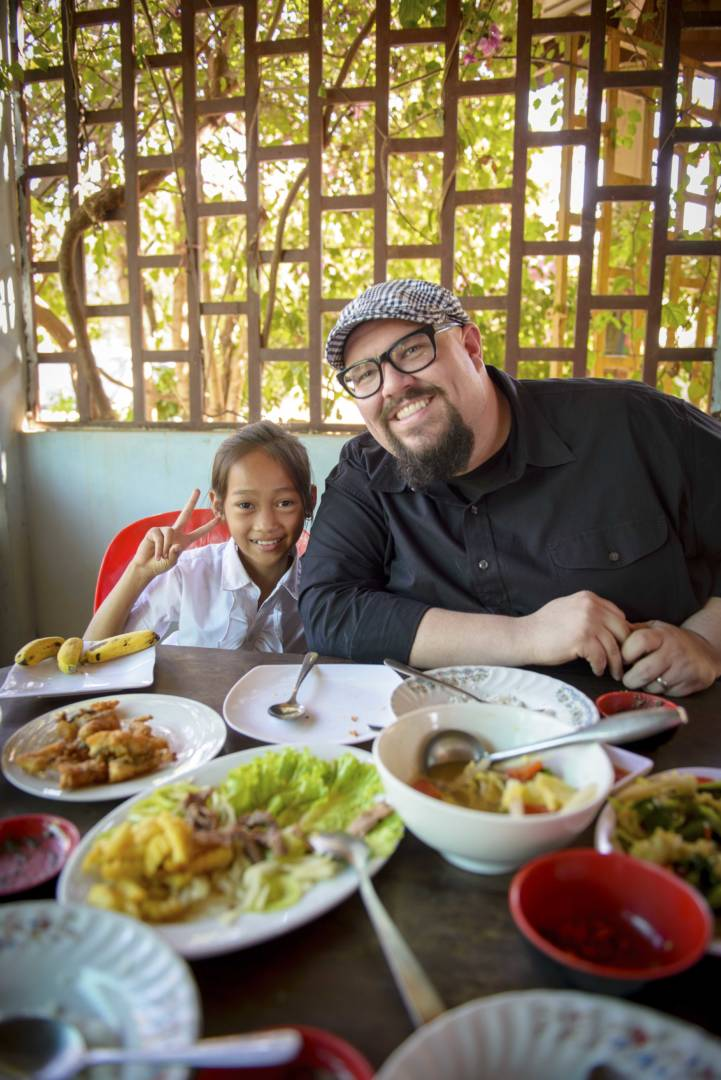Mike Weaver, singer for Big Daddy Weave, eats lunch and shares family photos with his sponsored child, Kimhuoy Hak and her family.