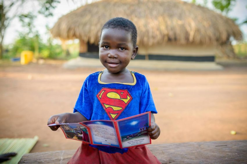 Superheroes. Defin, 3, looks at a Christmas card her brother, Joshua Ogwang, 10, received from his sponsors, who live in California. (©2014 World Vision/photo by Jon Warren)