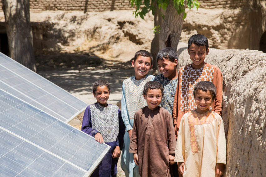 Clean water. Children stand by a solar panel that powers a drinking water decontamination system in the Langar district in Afghanistan. Before World Vision installed the system, they had to walk 30 minutes to reach a dangerously contaminated water source. (©2017 World Vision/photo by Narges Ghafary)