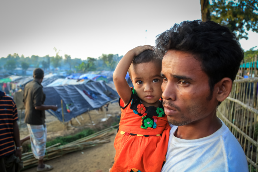 "Myanmar refugees in Bangladesh. Hossain holds Yasminara, his 1 ½-year old daughter, in a Bangladesh refugee camp. ""When it rains we all get wet,"" he says. (©2018 World Vision/photo by Shabir Hussain)"