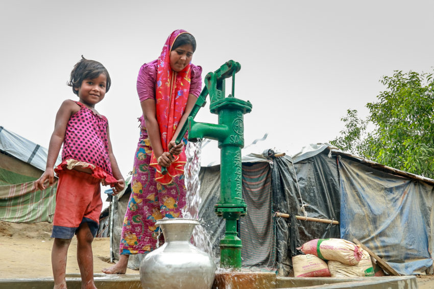 Myanmar refugees in Bangladesh. Nur Banu and her daughter, 7-year-old Jannat, fetch water from a tube well near their tent. World Vision installed the well in partnership with UNICEF. Before the well, she had to walk far and stand in line for water. She was afraid of being sexually assaulted when fetching water at night. (©2018 World Vision/photo by Joy Maluyo)