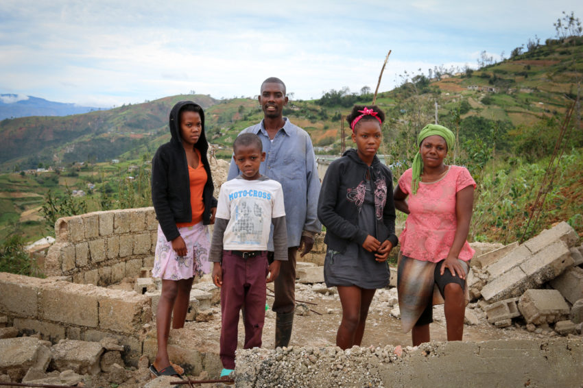 "After Hurricane Matthew in Haiti - ""We have lost all,"" says Enock, 42, standing with his family in the remains of their destroyed home in Kenscoff. From left to right: Taninia, 18; Enivens, 10; Enock; Bilandie, 15; and mother Nathalie. (©2016 Santiago Mosquera/World Vision)"