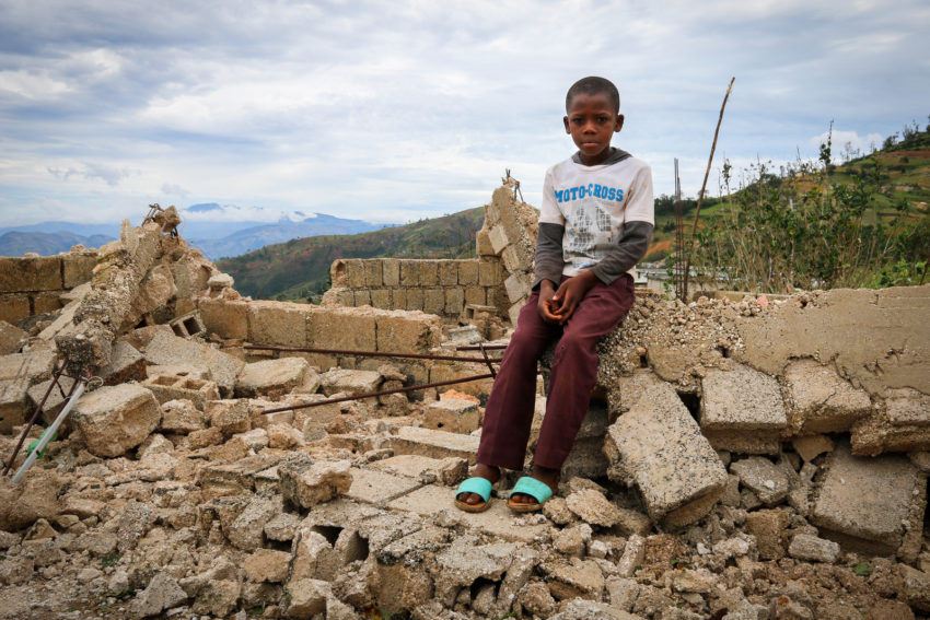 Enivens sits on the crumbled blocks that are all remaining of his family's home after Hurricane Matthew blew through Haiti. (©2016 World Vision, Santiago Mosquera)