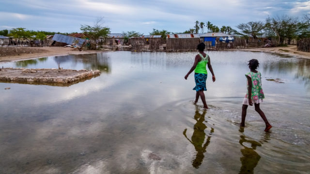 "Water inundates Boudain, a community on La Gonâve island, one of the areas hardest hit by Hurricane Matthew on the island nation. Ivonne and her daughter Cindia, 8, walk toward their collapsed home. ""I really do not know what I will do,"" she says. World Vision supports 100 children in Boudain through sponsorship and is bringing relief supplies. (©2016 Claudia Martinez/World Vision)"
