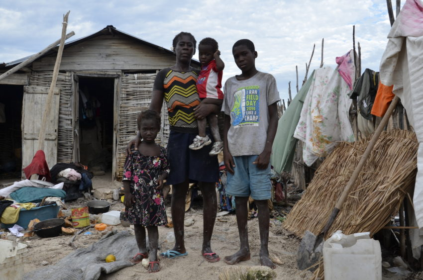 "In Haiti, Marie holds her baby and stands by her older children, Lanchise, 4, and Narcise, 14, next to their few possessions. ""I was trying to build a house, but it fell down with the hurricane,"" she says. Hurricane Matthew also destroyed the goods she sells. She doesn't have money to begin again. (©2016 Claudia Martinez/World Vision)"