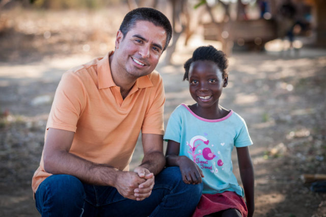 Edgar Sandoval poses with 8-year-old Faith, his World Vision sponsored child, in Kapululwe, Zambia.