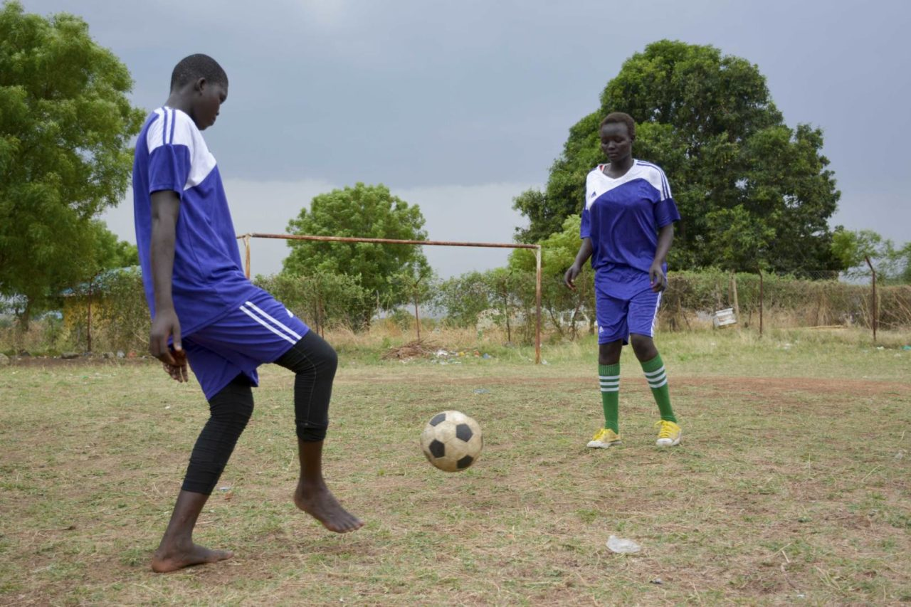 Two girls kick a soccer ball back at a Child-Friendly Space in South Sudan.