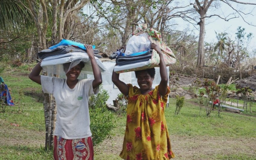 2015 Cyclone Pam_Vanuatu_Two women carry home household goods from a World Vision relief distribution on Tanna Island, Vanuatu. (©2015 World Vision/photo by Gabrielle Brophy)