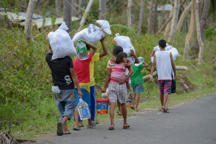 2013 Typhoon Haiyan_Philippines_families carry relief supplies. It laid waste to the country's central region, killing more than 6,000 people and leaving more than 4 million people homeless and hungry.