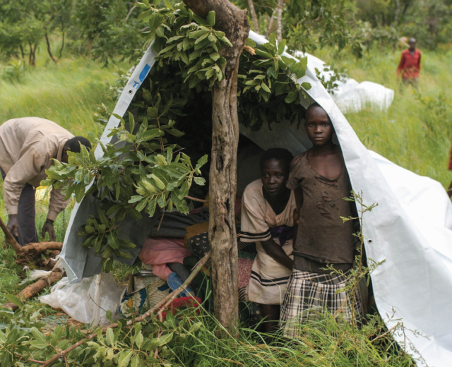 A family from South Sudan takes shelter from an oncoming storm just a few days after they arrive in Uganda.