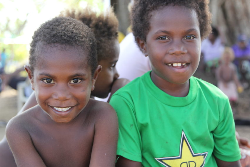 2015 Cyclone Pam_Vanuatu_Though their village near Port Vila was destroyed by Cyclone Pam, Brian, 5, and Denisha, 6, show that, like their country's welcome banner, #Vanuatustillsmiles. World Vision distributed tarps, kitchen kits, and hygiene kits to the village so families could patch up their homes, boil water, and help prevent the spread of disease. (©2015 World Vision/photo by Andrea Swinburne Jones)