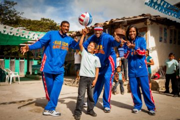 Harlem Globetrotters players pose with a boy during a visit to World Vision project areas in Honduras.