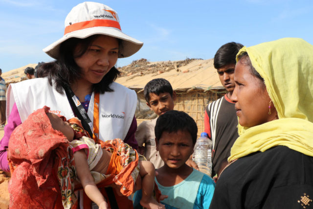 World Humanitarian Day: World Vision Regional Field Director Buli Hagidok holds a baby as she talks with a refugee family in a camp in Bangladesh. Home to 886,000 refugees, this camp is the largest, most densely populated in the world.