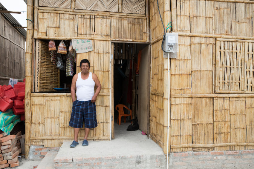 2016 Ecuador earthquake destroyed Juan Baptita's house. He stands in front of a shop and temporary house built with money from a cash aid program by World Vision.
