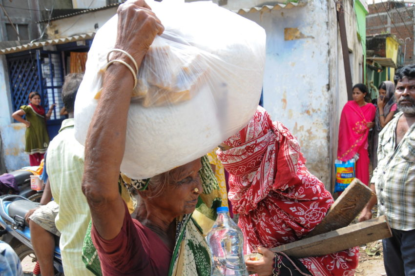 After Cyclone Phailin hit their community in 2013, women carry a relief pack of dry rations from a World Vision distribution for families.