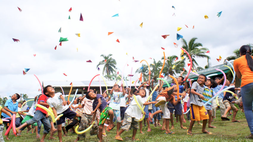 More than 3,500 children attended World Vision's Child-Friendly Spaces to play and heal after Typhoon Bopha in 2012. They throw paper airplanes in the air as a symbol of their hopes and dreams for the new year.