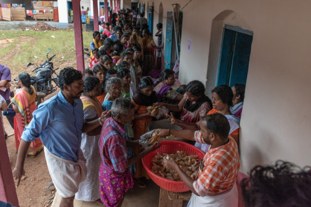 2018 India floods. More than 450 families whose houses have been flooded are taking shelter in a secondary school in Pathanamthitta, Kerala. Representatives of each family stand in long lines to receive food. Heavy monsoon rains led to flooding, and now that dams have been opened every, house in the community is submerged. (©2018 World Vision/photo by Theodore Sam)