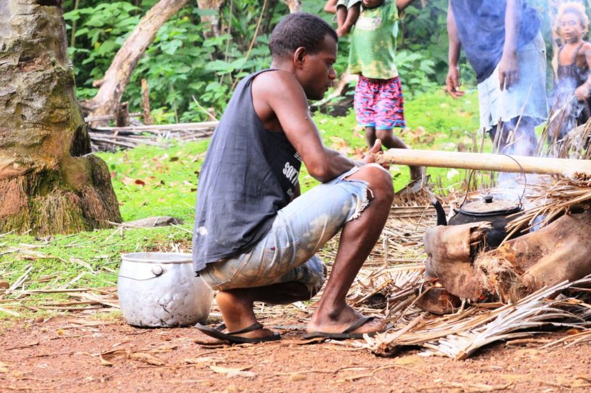 A young man boils water over a fire during a disaster simulation in Tetupa, Solomon Islands. Six communities in north eastern Guadalcanal province participated in flood simulations to help them prepare for emergencies. These communities are particularly prone to flooding.