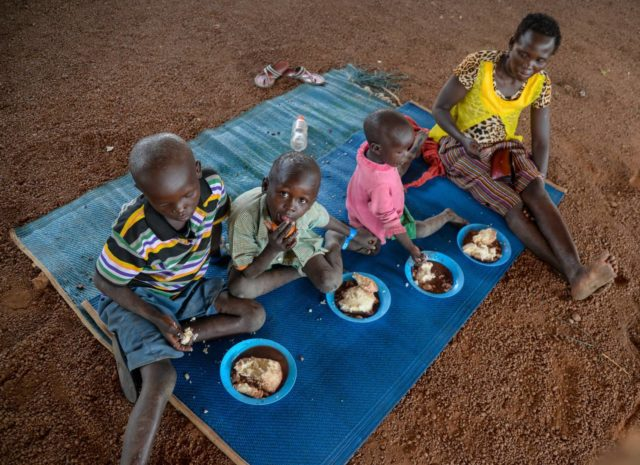 Rose and her children enjoy their first real meal in weeks at the Goboro transit center in Uganda. This hot meal was provided by World Vision for Rose's family and hundreds of others on their way to more permanent shelter for refugees from South Sudan. (©2018 World Vision/photo by Moses Mukitale)