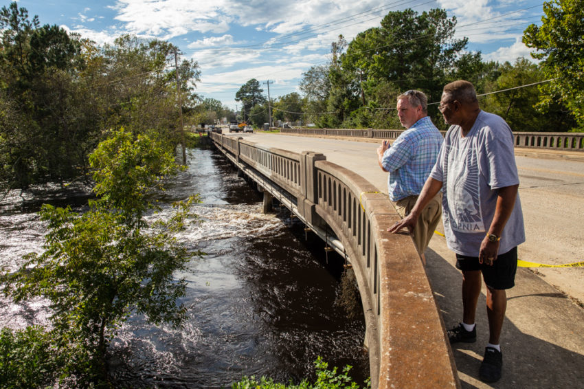 Two men stand on a bridge in Lumberton, North Carolina, surveying the flooding from Hurricane Florence.