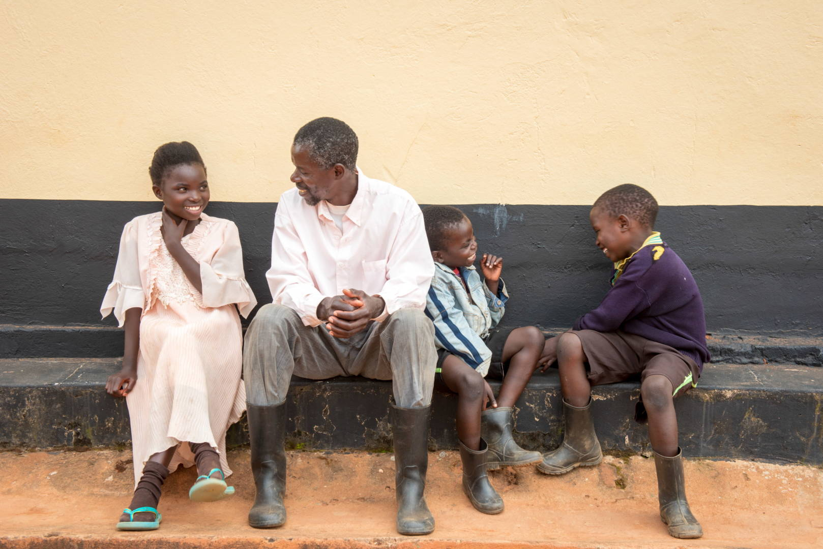 Loveness sits with her father, Ignatius and her two younger brothers--Adam, 5, and Cacious, 8.