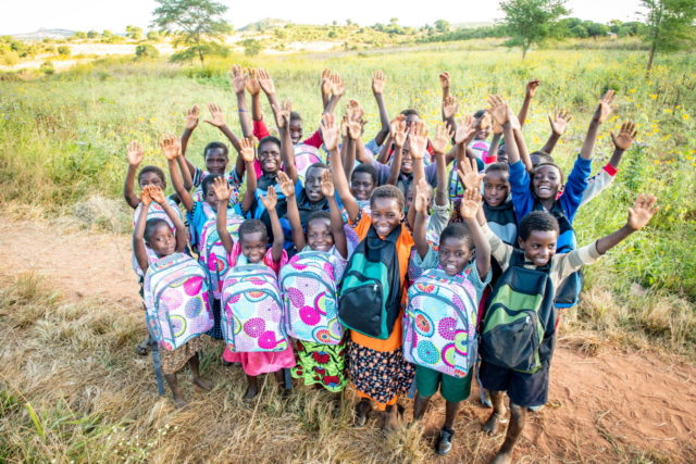 A group of children in rural Zambia celebrate their newly received backpacks with arms raised.