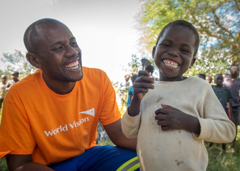World Vision Zambia staff member, Matthew Sakala helps Adam, age 5, with his piece of birthday cake at the community-wide birthday celebration hosted by World Vision.