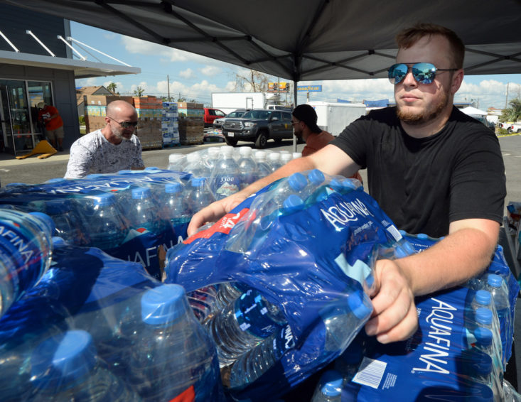 Jayson Roach stacks water at Northstar Church in Callaway, Florida on Wednesday, October 17, 2018. A steady stream of vehicles were seen throughout the day at the church as impacted families received items donated by World Vision and others.