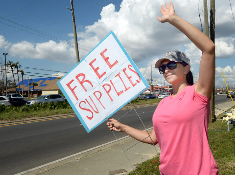 Carolina Koval waves to passers-by at Northstar Church in Callaway, Florida on Wednesday, October 17, 2018. A steady stream of vehicles were seen throughout the day as impacted families received items donated by World Vision and others.