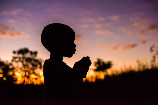 A sponsored child in Zambia is silhouetted against the sky.
