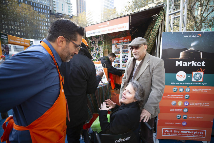 Crystal Sada, 59, and her husband Jai, 60, share with World Vision staff member Javy Diaz about how they were drawn in like a magnet to World Vision's Give-back Gift Shop.