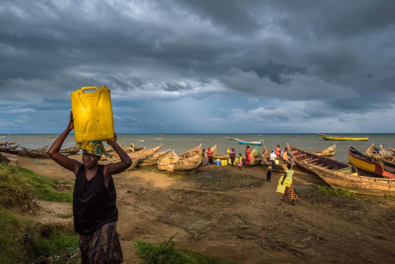 A woman fetches water from Lake Albert, Uganda, in a fishing village where World Vision provides healthcare. On the opposite shore is the Democratic Republic of the Congo. In the midst of storm clouds, a brief shaft of sunlight breaks through.
