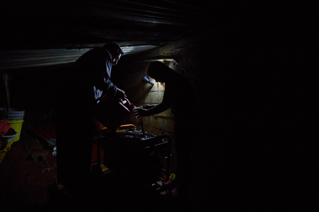 "Tomas Gonzalez Cruz, 68, left, and his granddaughter, Kimberly Montalvo Gonzalez, 23, fill their family's generator with gasoline by the light of a portable solar lamp behind their house near Utuado, Puerto Rico. Like many in rural areas, Tomas' family lived without electricity and clean water for months after hurricanes Irma and Maria devastated the island territory. Ultimately, they survived 11 months without power. The nearly 5 gallons of fuel per day allowed them to care for the two special needs adults and extended family living with them, but proved very costly. Tomas' wife Ana moved me with her faith and determination in the midst of their struggle. ""I was born here, grew up here, raised my kids here,"" Ana says. ""We're also pastors. We have to stay and face the situation because so many others lost everything."""