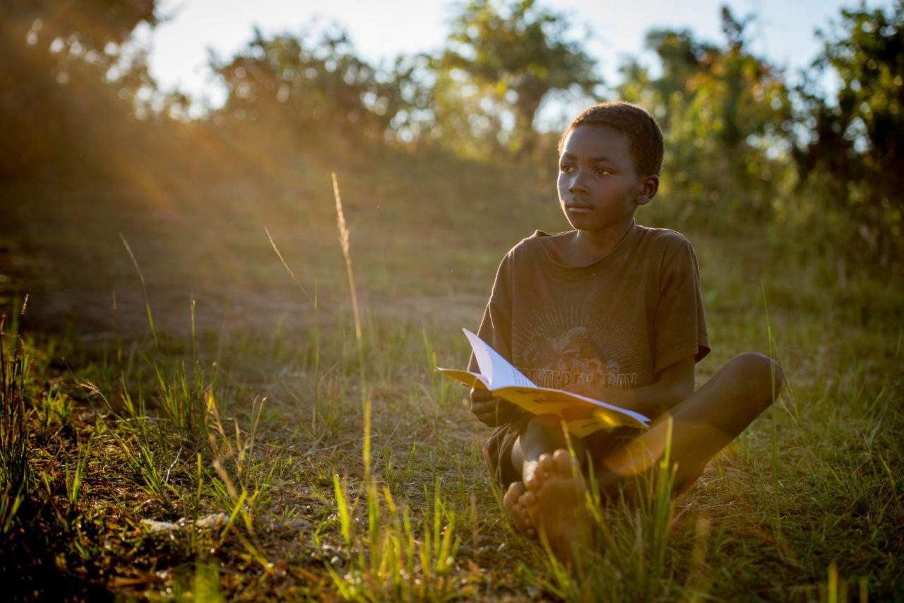 While waiting for a group photo, 11-year-old Lightwell took the opportunity to read his book — something he sometimes chooses over eating. I glanced up and saw the golden afternoon sun lighting him so beautifully and was able to grab this quiet portrait of a boy from Zambia and his favorite pastime.