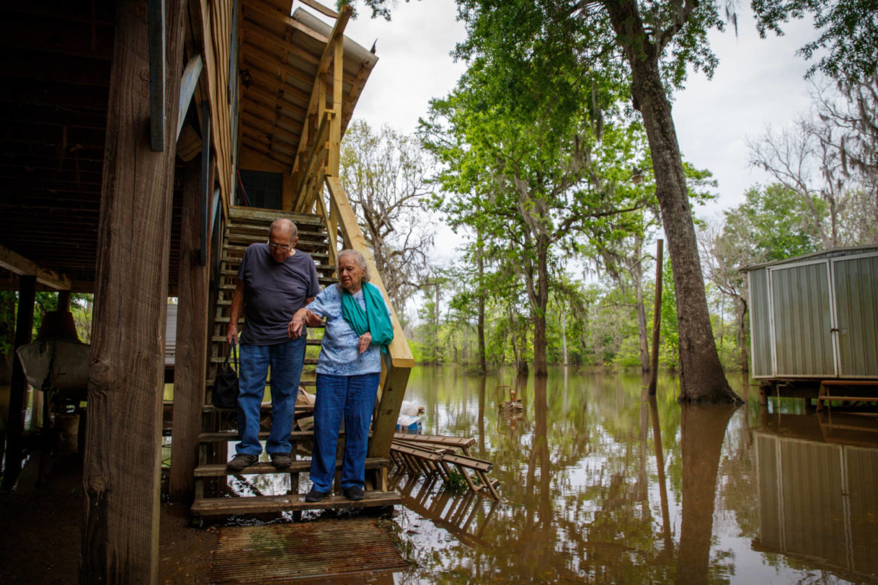 "In April, John Harris helped his wife, LaDell, down the steps in front of their home along the shores of the Neches River near Vidor, Texas. She had slipped and hurt her arm while waiting days for floodwaters to clear from the porch steps. Their home was nearly destroyed by 15-foot floodwaters during Hurricane Harvey in August 2017. World Vision and its local partner, Wings of Promise led by Pastor Skipper Sauls, helped the couple rebuild with new appliances, Sheetrock, furniture, insulation, light fixtures, and other materials. John and LaDell were able to enjoy their cozy rebuilt riverside home together for a few more months in 2018 before John lost his fight with cancer in August. ""During the storm, we were sitting here, helpless,"" LaDell says. ""These people (Pastor Sauls, and other community members) have been our angels."""