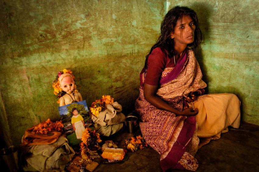 After the 2004 Indian Ocean tsunami, Arahi Japanthan, 26, sits next to a shrine in her home in memory of her youngest daughter, Snega, 3, who died in the tsunami. Snega and 5-year-old Abineha couldn't keep up with their older sister when the three girls fled the rushing water that struck their coastal village in southeast India.